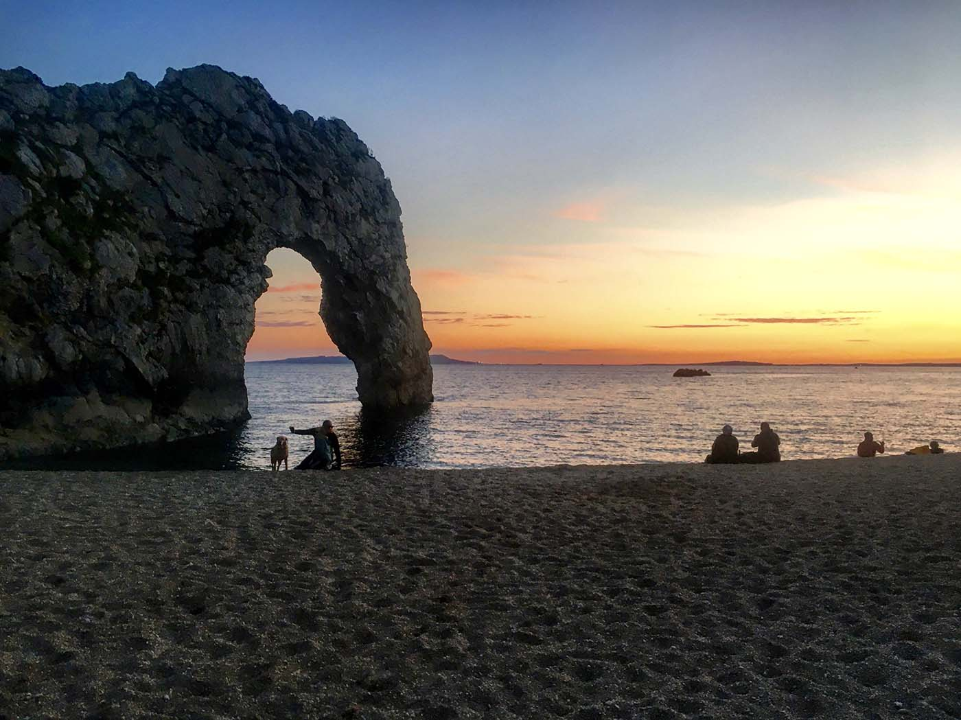 Photo of a beach at sunset with some people and a dog enjoying the view.