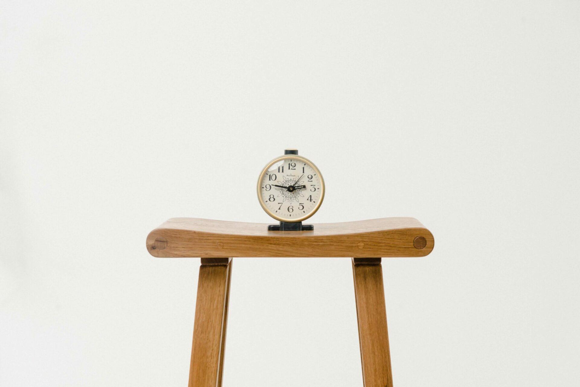 An alarm clock sitting on a stool