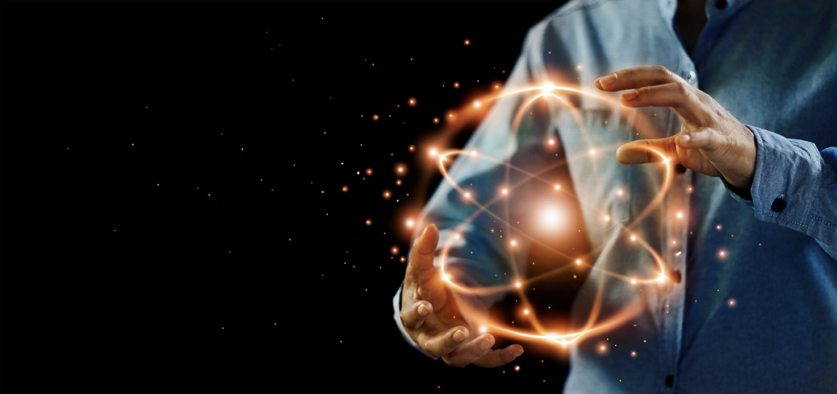 Abstract science, hands holding atomic particle, nuclear energy imagery and network connection on dark background.