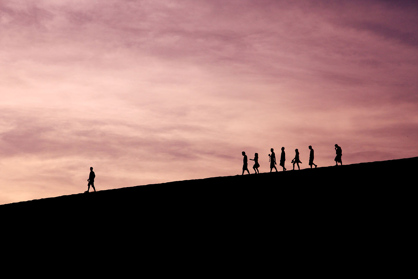 Person standing ahead of a group, leading them forward.