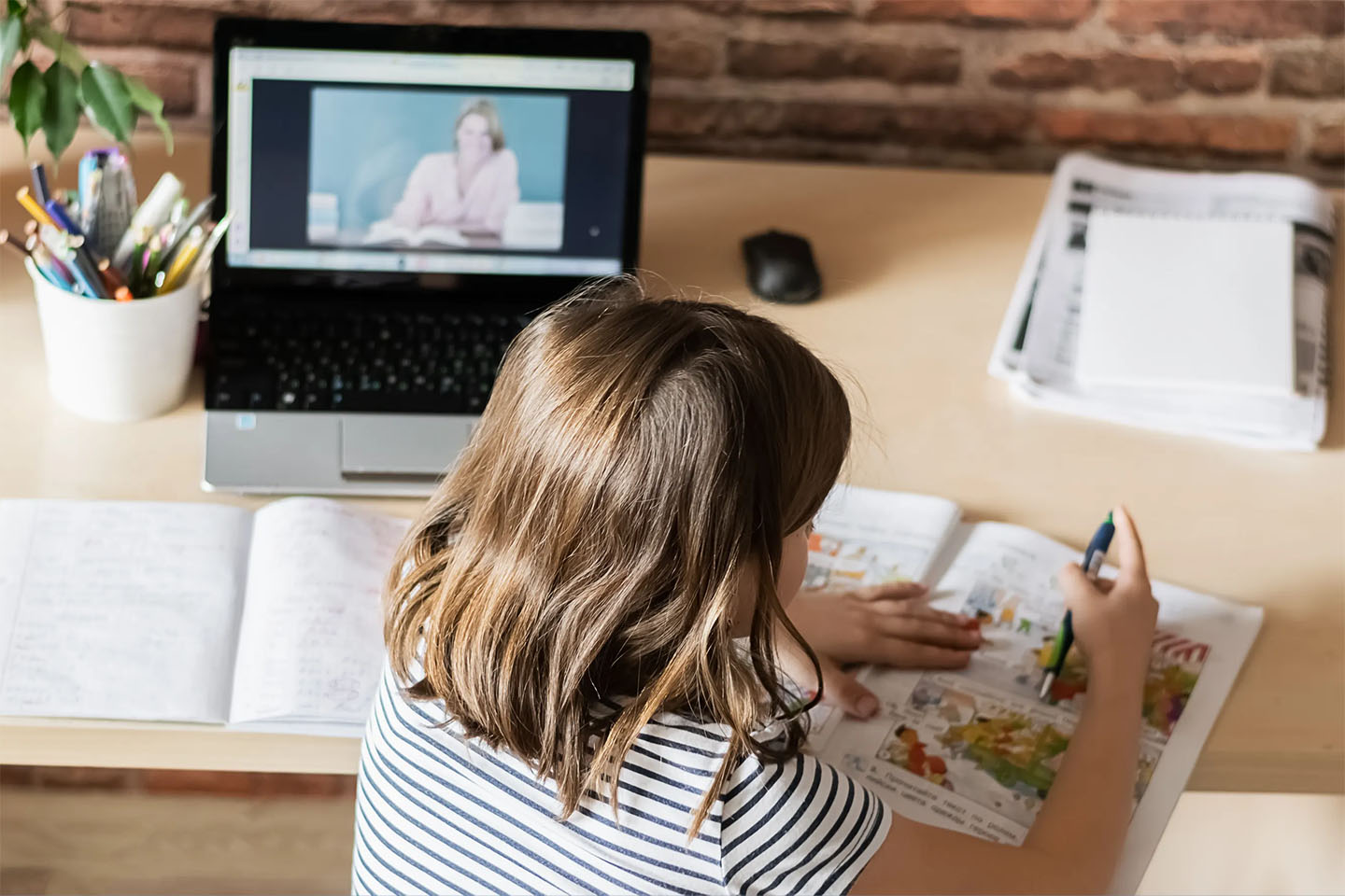 The concept of distance online learning self-isolation. Child sitting home desk doing lessons through a digital laptop.