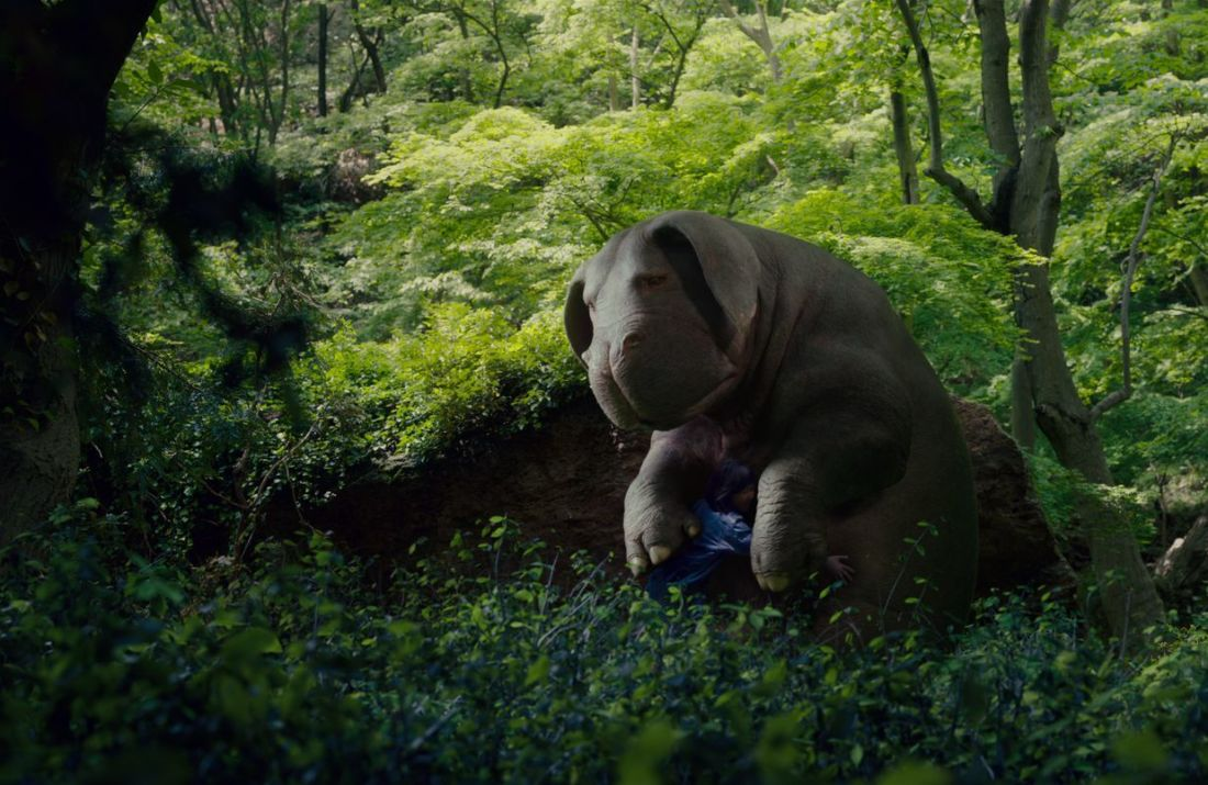 Photo from the film Okja depicting the super pig and the little girl hugging