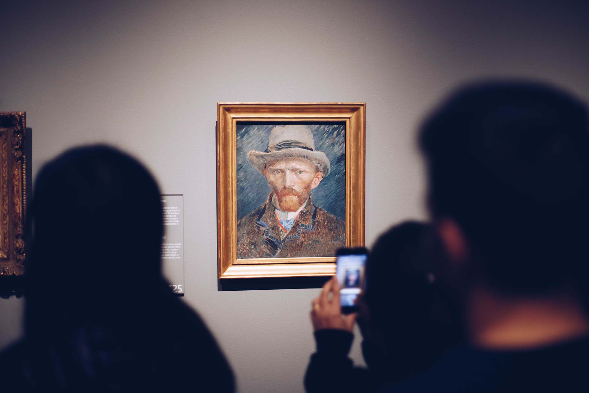 Photo of someone taking a picture of a Vincent VanGogh portrait in a museum.
