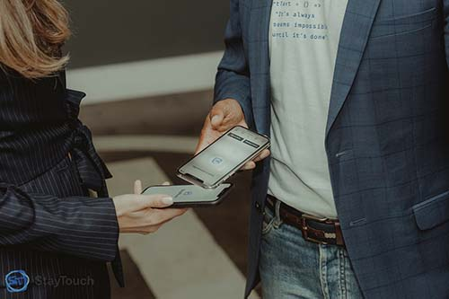 Photo of two people using the StayTouch app at a conference.
