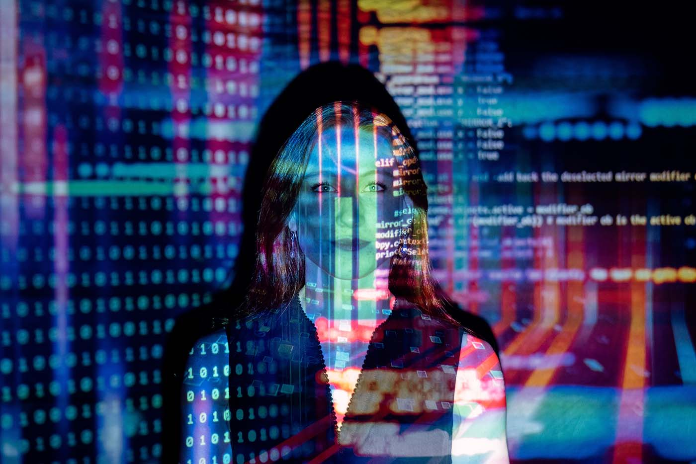 Women in tech and science. Photo of a woman with code projected on to her face.