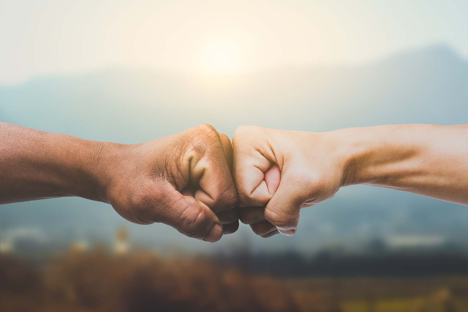 Man giving fist bump in sun rising nature background.